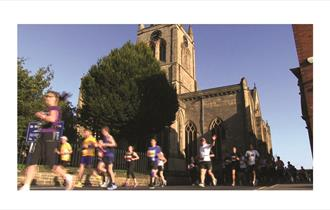 Runners passing the Crooked Spire